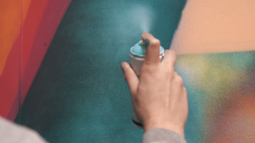 Graffiti artist painting on the wall, interior, close up, slow motion