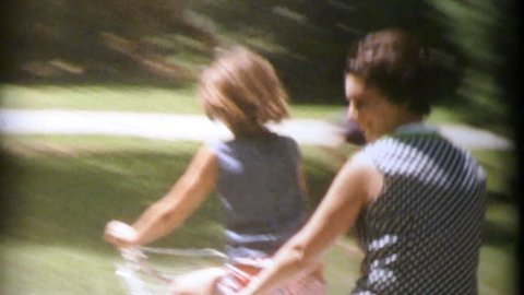 MADISON, WISCONSIN, JULY 1964:  A fun clip with various family members and friends riding past on a tandem bike in the summer of 1964.