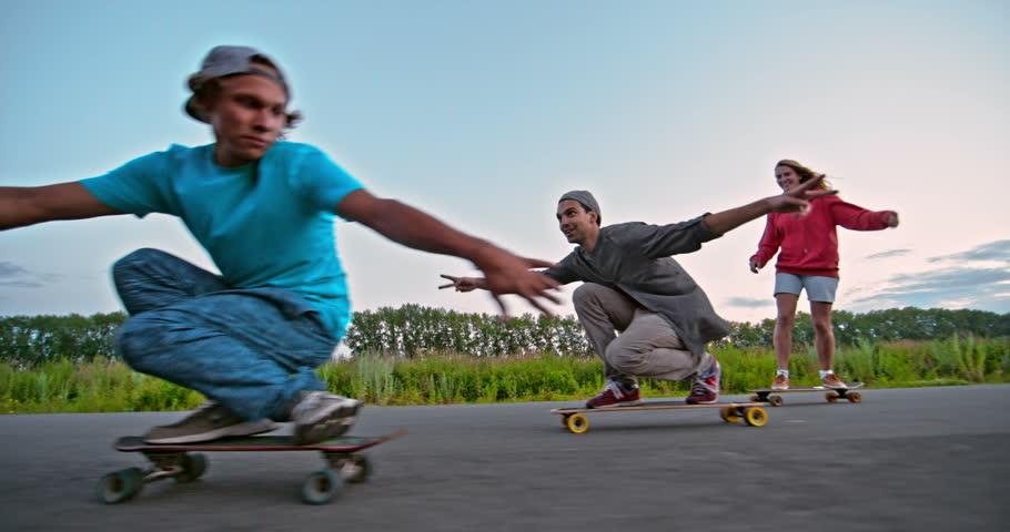 Joyful friends enjoying their longboard ride