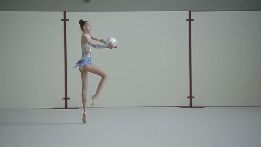 Rhythmic gymnastics: Teenager training a gymnastics exercise with a ball. Slow motion