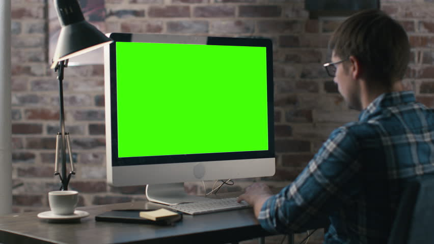Young man is working on a computer with a mock-up green screen. Shot on RED Cinema Camera in 4K (UHD). | Shutterstock HD Video #12943328