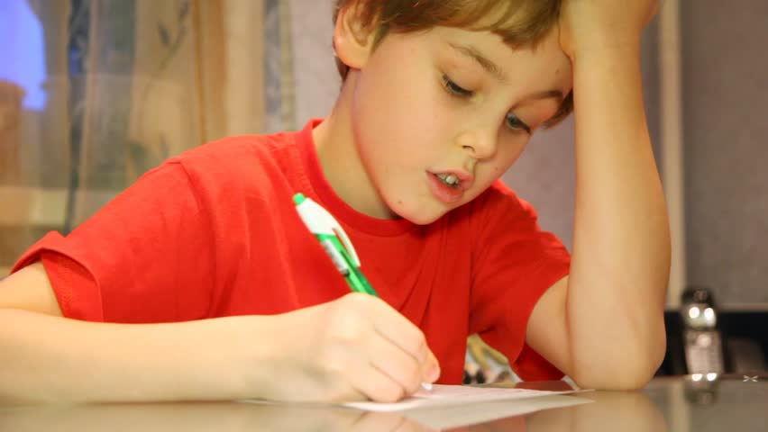 Close-up of serious boy very attentively writes something