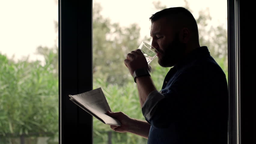 Young, handsome man drinking water and reading newspaper by the window