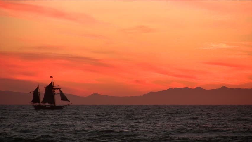 A tallship sailing across the sea at sunset