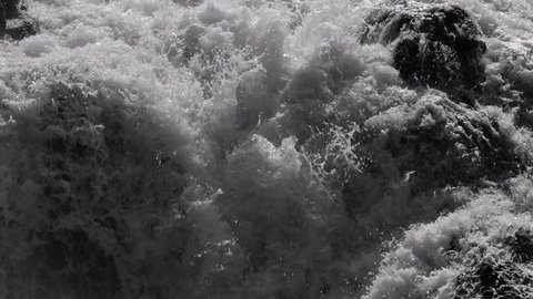 Dark dangerous white water in river flowing over rocks in slow motion