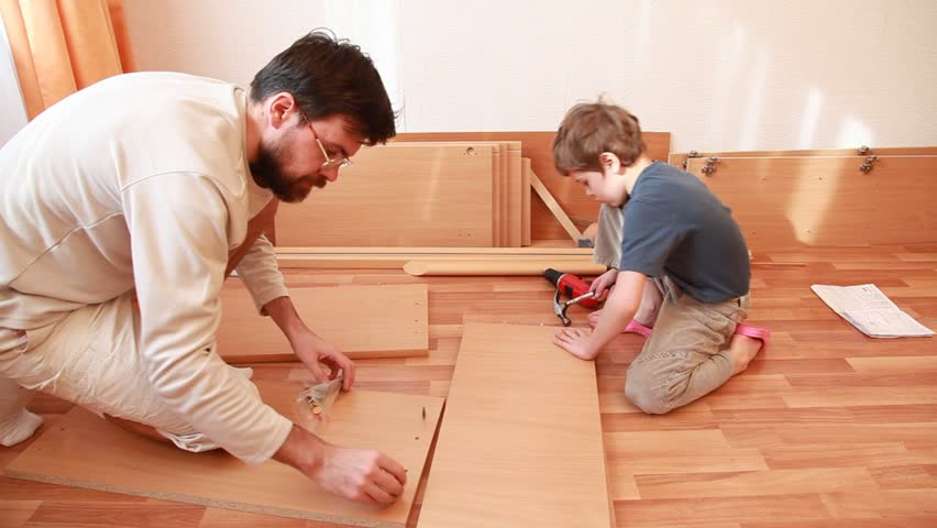 Father tightening screws in wooden board and little boy works with hammer sitting on the floor