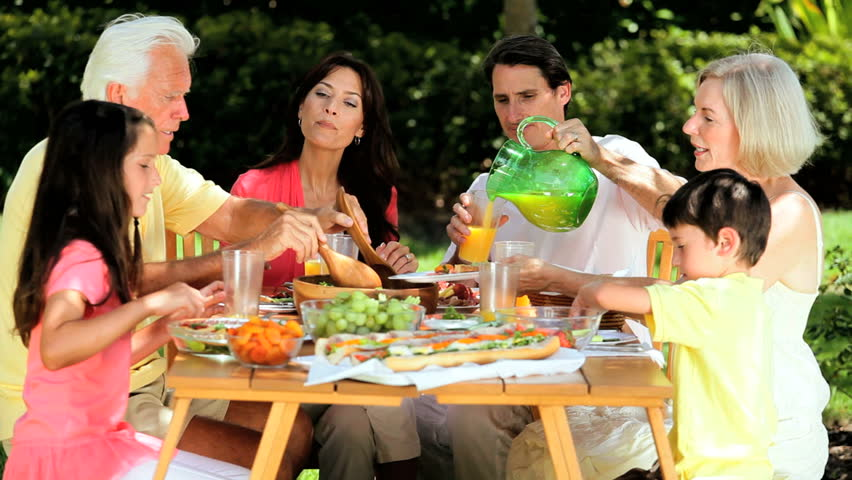 Three generations of caucasian family sitting outdoors sharing a healthy lunch together | Shutterstock HD Video #1302301