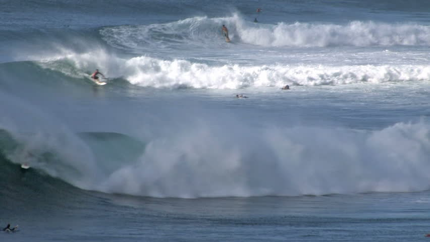 Surfers in big waves on Maui Hawaii tracking video. Waves curling into a pipeline look. Beautiful blue azure water. Breaker with white splash. Point of land with trees on northwest shore of Maui.  | Shutterstock HD Video #130411
