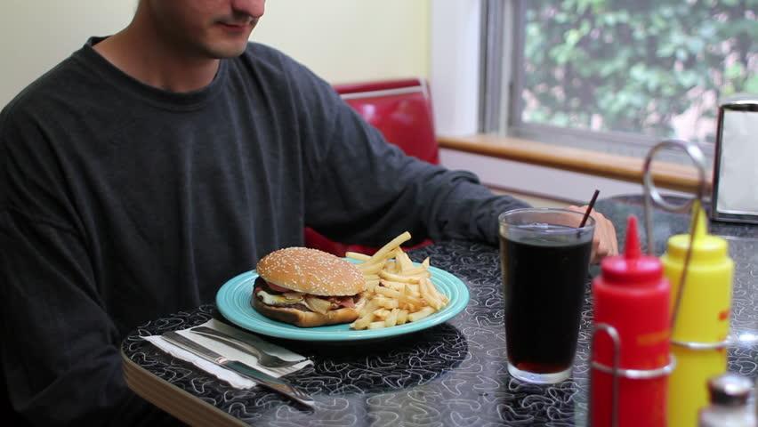 Unhealthy Eating, man eating fast food hamburger