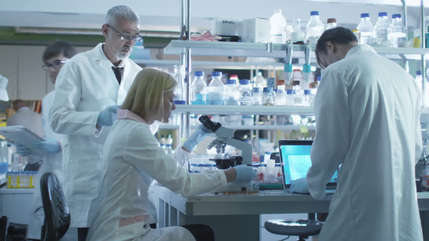 Team of scientists in white coats are working with a laptop and tablet in a laboratory. Shot on RED Cinema Camera in 4K (UHD).