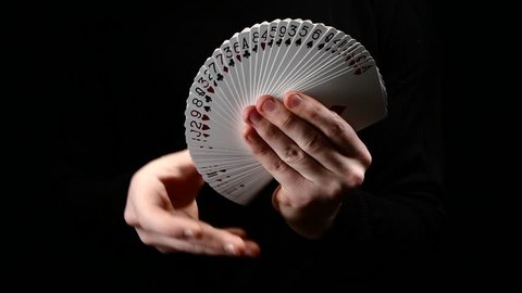 Talanted magician showing his trick with usual cards, like fan on black background, close up, slow motion
