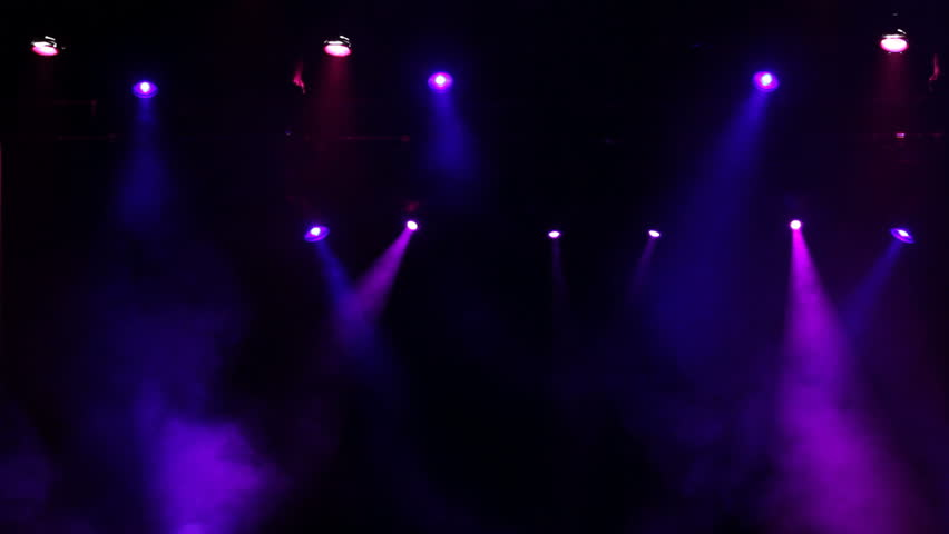 An extreme wide shot of a real concert stage with lights and smoke. Could be used as a background or as an overlay.