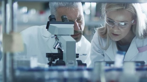 Male and female scientist are working with a microscope and a tablet in a laboratory. Shot on RED Cinema Camera in 4K (UHD).