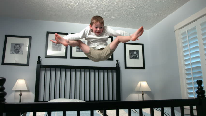 Cinemagraph - Young boy jumps on bed, slow motion. Looping Motion Photo.