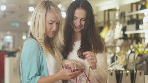 Two young happy girls are using a smartphone in a department store. Shot on RED Cinema Camera in 4K (UHD).