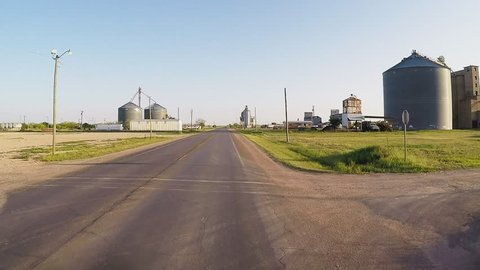 CROWELL, TX/USA - August 3, 2015: POV driving by a modern farm at sunset. A driver's point of view passing grain silos and other farm related equipment and agricultural buildings.
