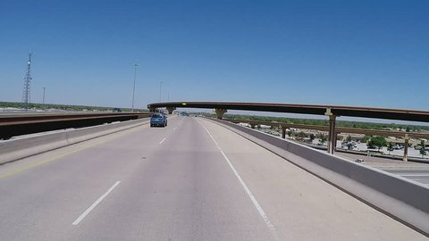 LUBBOCK, TX/USA - July 11, 2015: Point of view vehicle driving shot of driving on a new freeway ramp. A traveler's viewpoint of passing over and through an overpass and freeway interchange.