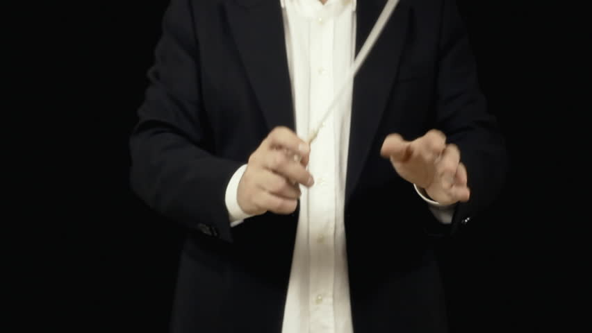 The conductor of an orchestra directing the musicians (medium shot, no face). Conducting: directing a musical performance with visible gestures.    Shutterstock HD Video #13122971