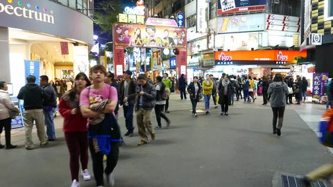 TAIPEI, TAIWAN - FEBRUARY 13, 2015: Ximen district area, overcrowded in night time. Tuxury downtown lifestyle at ximending, swarm of different people walking on pedestrian area, brightly illuminated