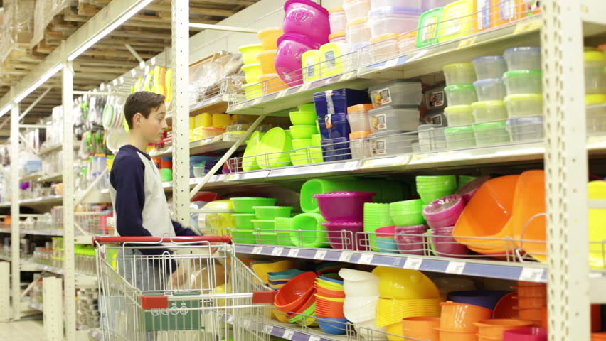 Teenager boy in the store chooses green container for food and puts it into the cart | Shutterstock HD Video #13167521