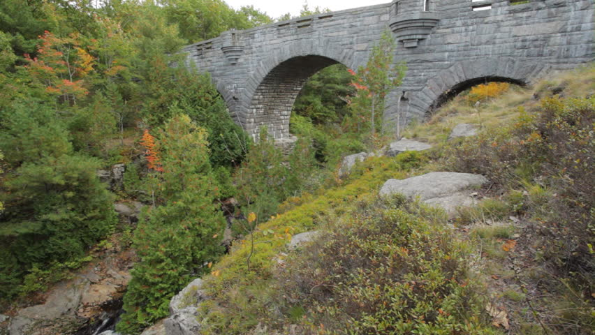 One of the carriage road stone bridges in Acadia National Park in Autumn. The clip begins on  Duck Brook Bridge, and pans to Duck Brook amidst colorful Fall foliage.