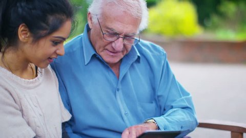 4K Caring young home support worker showing elderly gentleman how to use a computer tablet. Shot on RED Epic