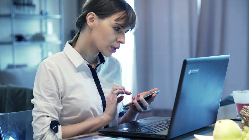 Busy, multitasking businesswoman working by table at home