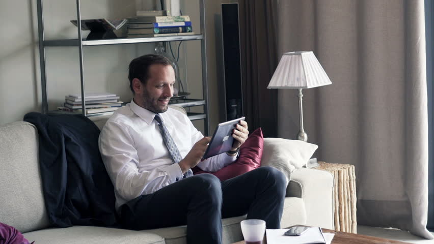 Businessman with tablet computer sitting on sofa at home    Shutterstock HD Video #13207391