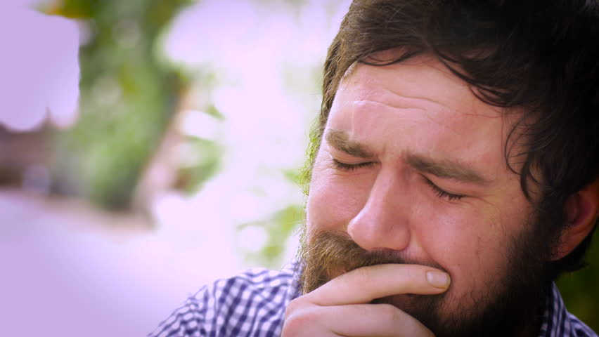 Close up portrait of a young hipster man with a full beard who is severely depressed and sad. He is holding back tears and could even be suicidal.