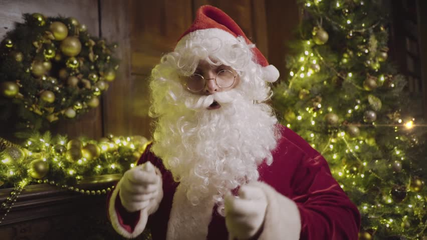 Santa Claus in eyeglasses blowing snow, sending kiss and looking at camera, decorated fireplace and christmas tree on background