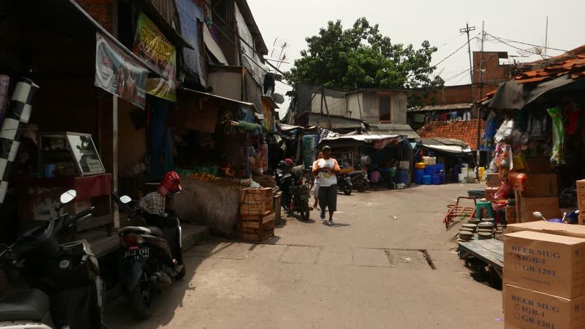 JAKARTA, INDONESIA - MARCH 09, 2015: Slum area around Pasar Ikan and fish market, old town near Sunda Kelapa harbor. Camera walk into local houses and hovels district, sunny and empty street.