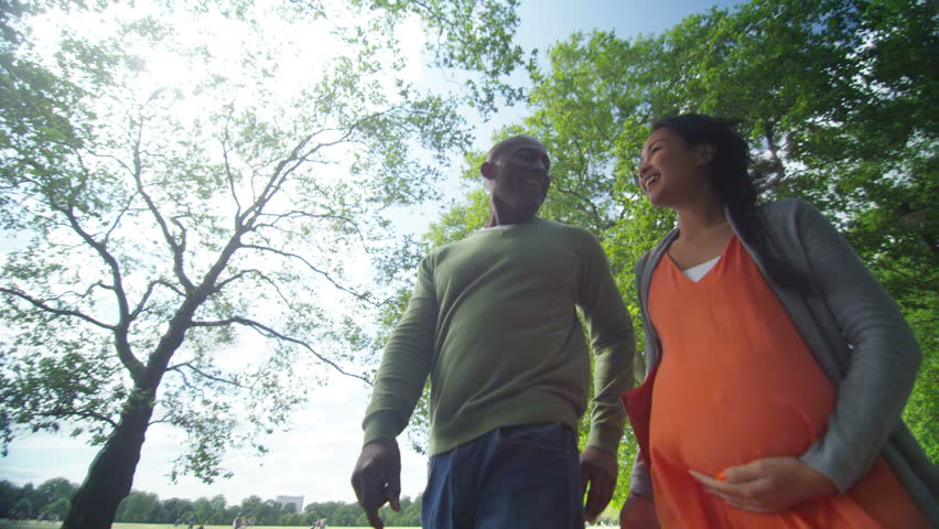 4K Happy mixed ethnicity couple expecting a baby, taking a walk in the park. Shot on RED Epic.