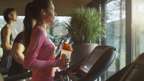 Fit athletic girl is drinking protein shake while exercising on treadmill in sport gym. Shot on RED Cinema Camera in 4K (UHD).