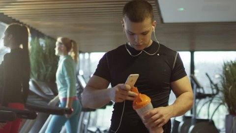 Young athletic man is listening to music on a smartphone while walking in sport gym with treadmills. Shot on RED Cinema Camera in 4K (UHD).