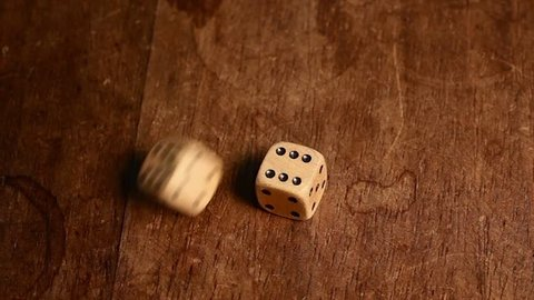 Double six (twelve) is rolled with two wood dices on a wooden table.