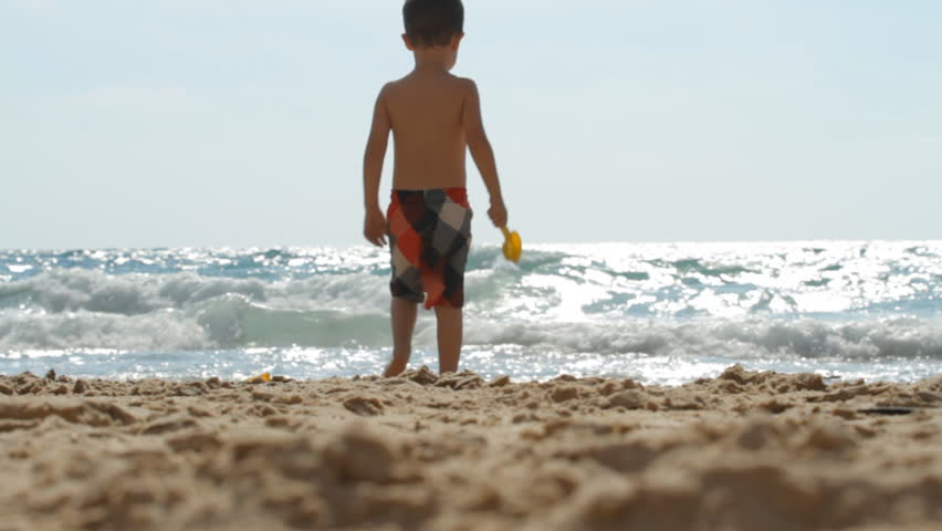 Boy playing on the beach and walking people