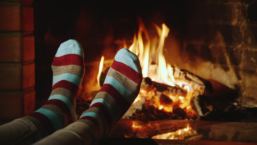 The Girl Warms His Feet By The Fireplace. Concept: Warmth And ...