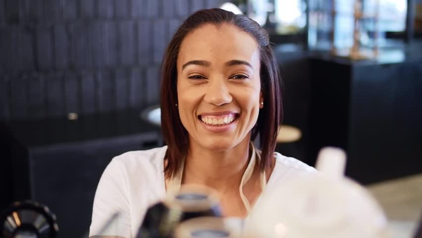 Smiling portrait of happy friendly approachable female woman barista in modern trendy coffee shop by the espresso machine | Shutterstock HD Video #13300601
