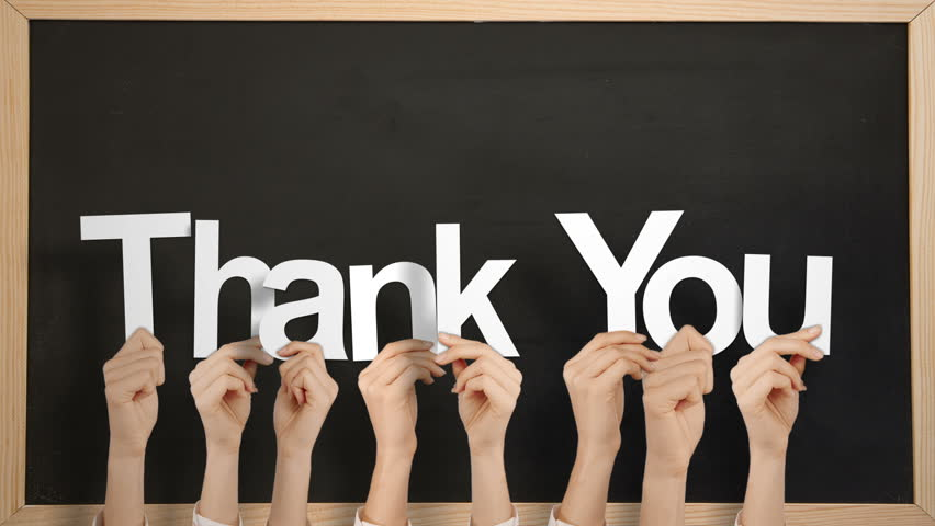 Hands Holding Up Gracias Against Chalkboard Stock Footage