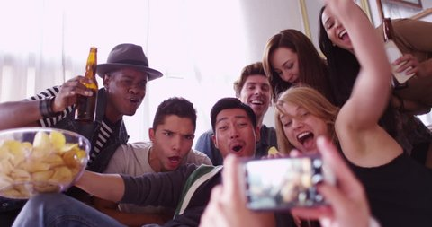 Group of friends having a party taking a photo with a smartphone laughing and smiling together