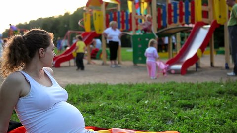 Pregnant woman looks at the children on the playground