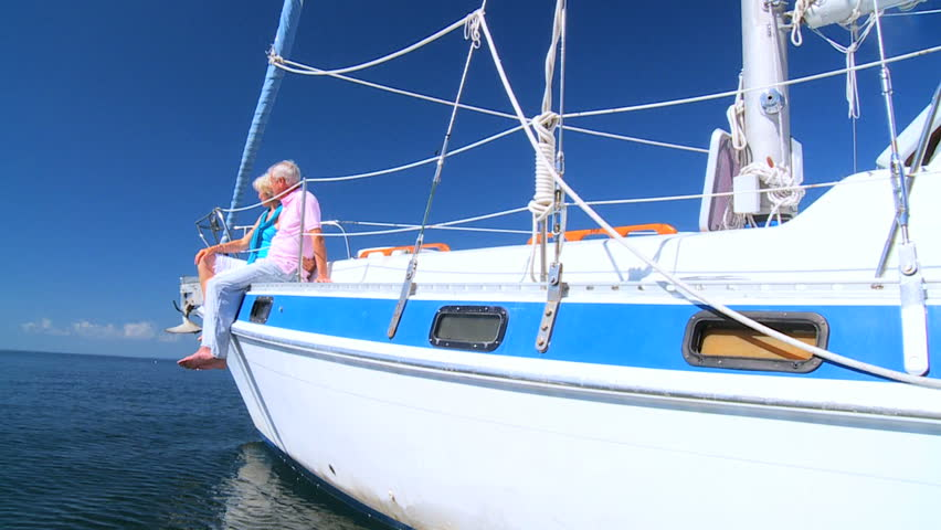 Healthy retired couple enjoying leisure aboard their luxury sailing boat filmed at 60FPS