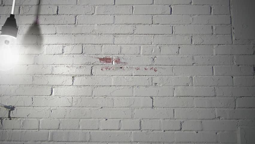 naked light bulb swinging against a white brick background