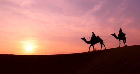 Silhouette of the Camel Trader crossing the sand dune during sunrise  at Thar Deset in Jaisalmer, India. Image is soft and contain noise due to high ISO used.