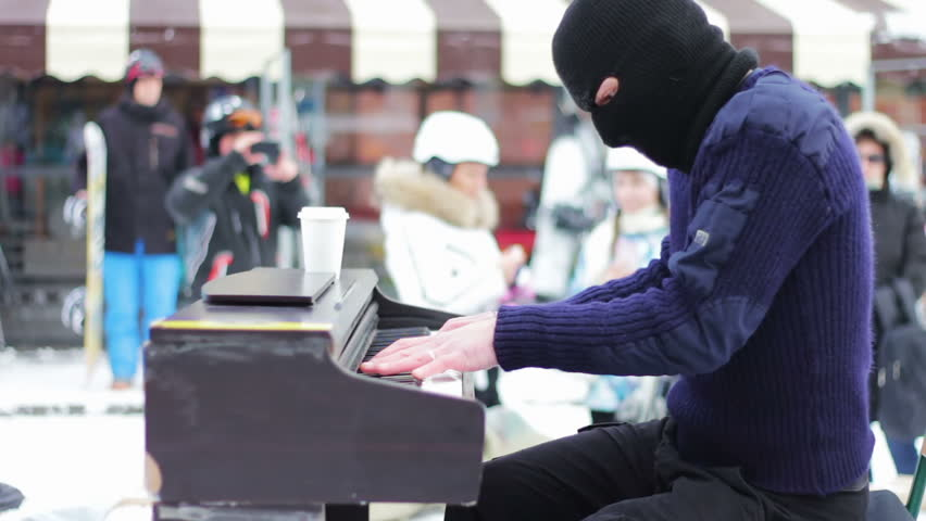 A man in a black mask plays piano sitting on a chair in the street among the people during the winter. | Shutterstock HD Video #13379921