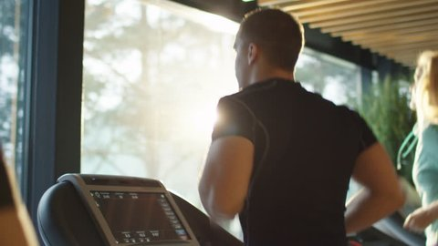 Young athletic men and women exercising and running on treadmill in sport gym. Shot on RED Cinema Camera in 4K (UHD).