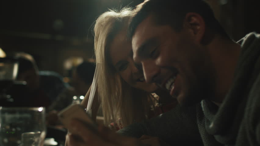 Friends laugh, drink beer and cocktails while having a good time together at a dark bar. Shot on RED Cinema Camera in 4K (UHD).