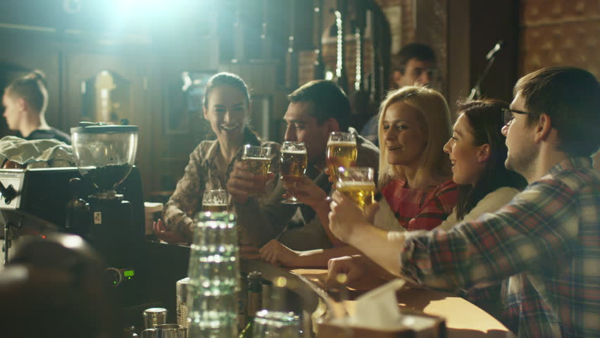 Friends laugh, drink beer and cocktails while having a good time together at a bar. Shot on RED Cinema Camera in 4K (UHD).