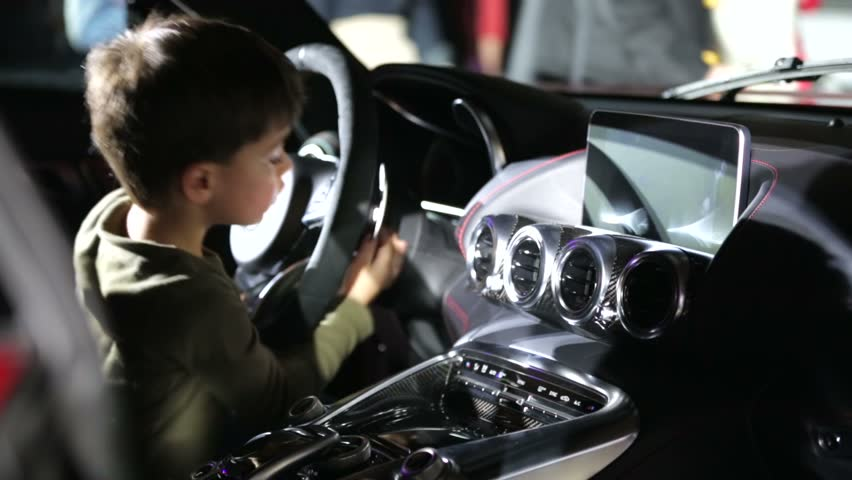 MOSCOW, RUSSIA - MARCH 29, 2015: Little boy tests Mercedes-AMG GT car, Mercedes-Benz Fashion Week. MBFW is a series of international fashion weeks sponsored by Mercedes-Benz and produced by IMG.