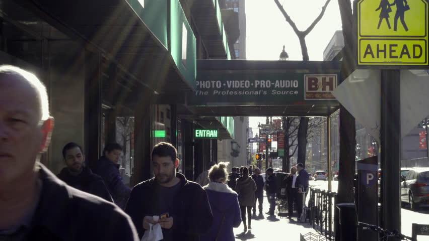 NEW YORK - NOV 29, 2015: People walking outside BH Photo Superstore, exterior shot on 9th Ave in 4K NY. B&H is a famous electronics store on 9th Avenue in Manhattan New York City.